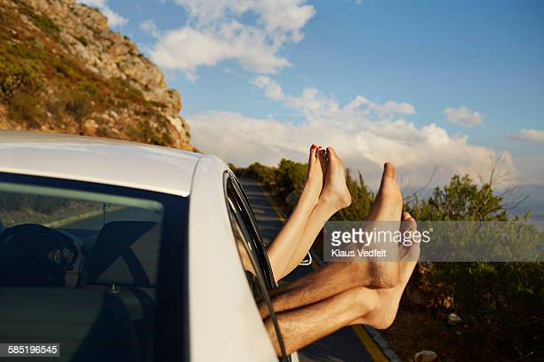 Couple relaxing with feet out of car window