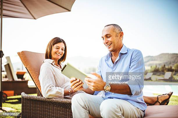 couple relaxing with multimedia device at the resort