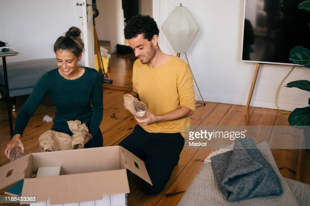 couple removing glasses from box in living room at new home - home ownership stock pictures, royalty-free photos & images
