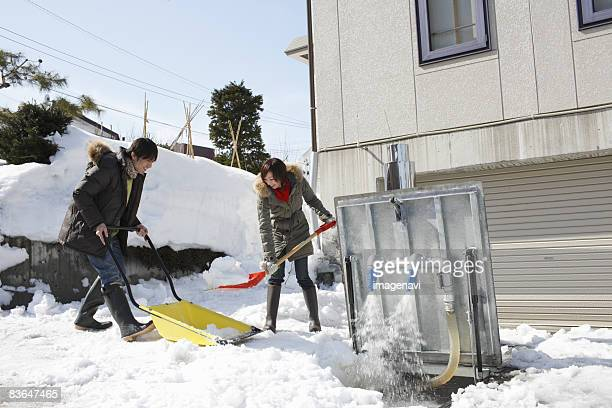 Couple removing snow