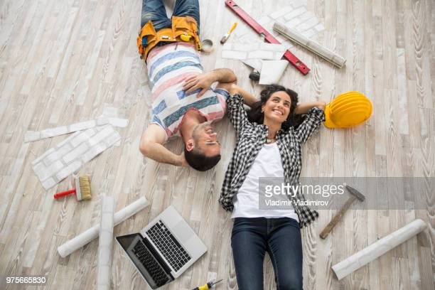 couple renovating and resting on floor - reform stock pictures, royalty-free photos & images
