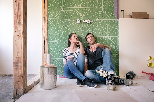Couple renovating new house, sitting on ground planning bathroom - gettyimageskorea