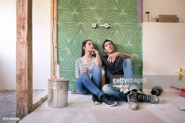 couple renovating new house, sitting on ground planning bathroom - renovierung themengebiet stock-fotos und bilder
