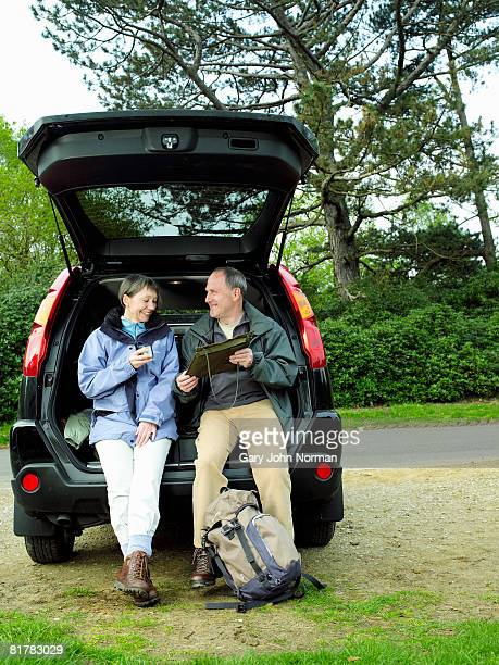 couple rest in back of car from hiking looking at map and having refreshment - king's lynn stock pictures, royalty-free photos & images