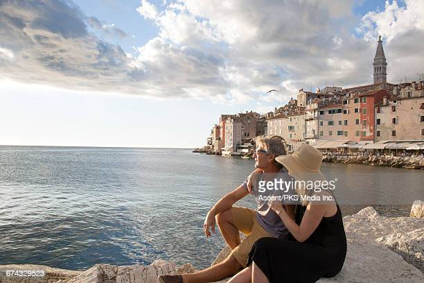 couple rest on rocks above sea, town behind - escapism stock pictures, royalty-free photos & images