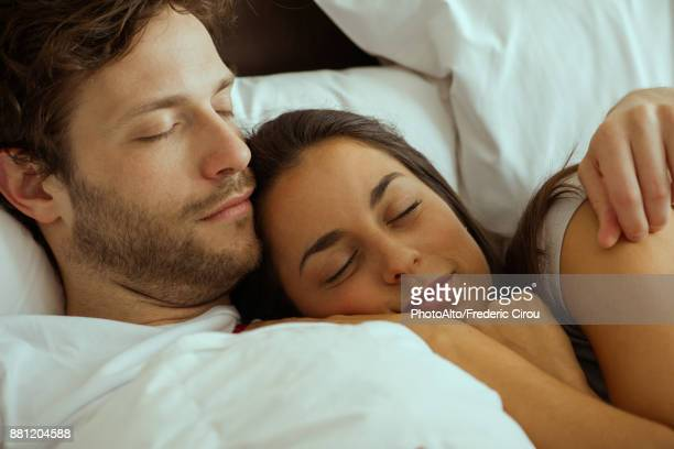 Couple resting and embracing in bed