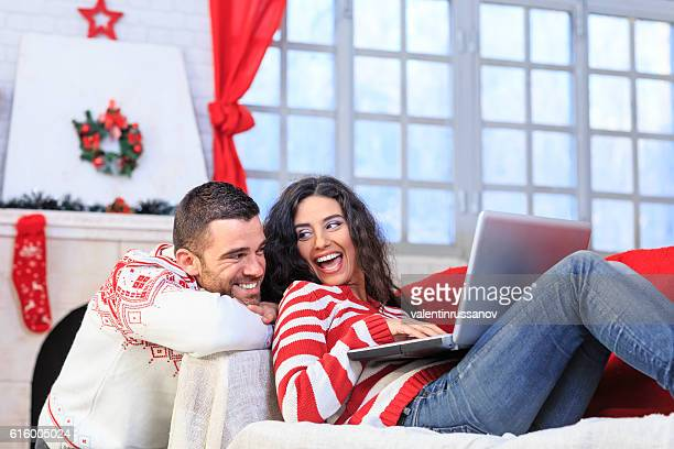 Couple resting at home and using laptop