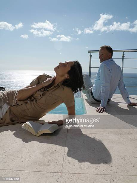 couple resting at poolside - fanny pic stock photos and pictures