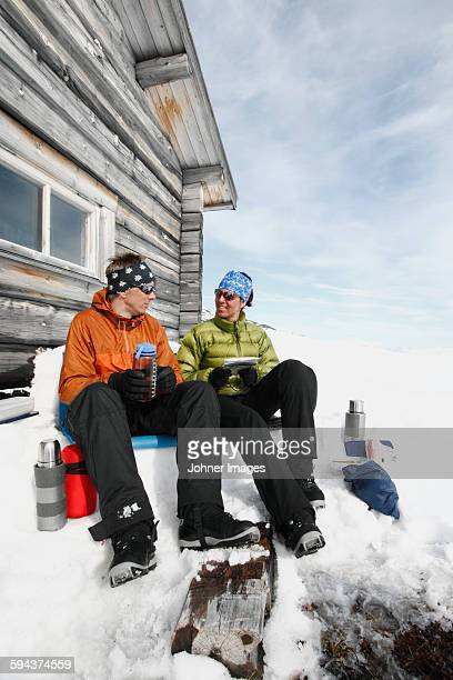 Couple resting in front of mountain cabin