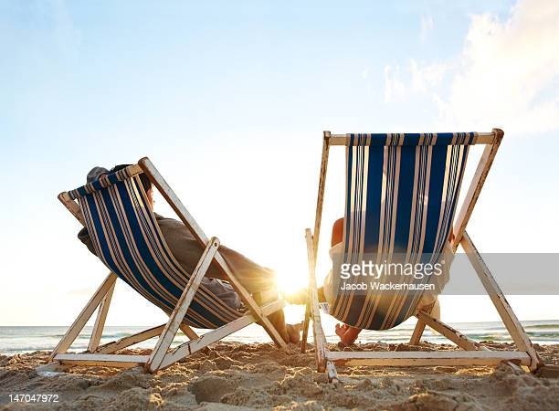 Couple resting on deckchairs at beach in sunset