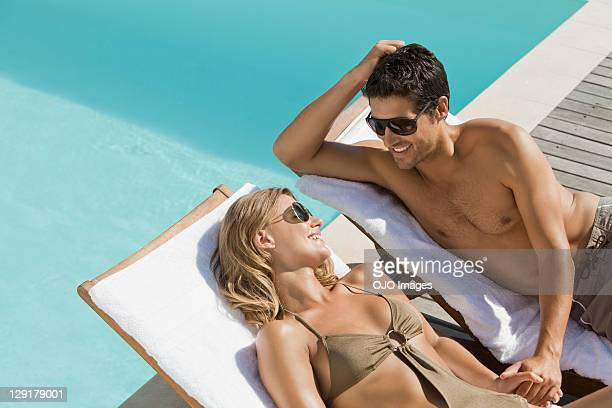 couple resting on lounge chairs holding hands - sunbathing stock pictures, royalty-free photos & images