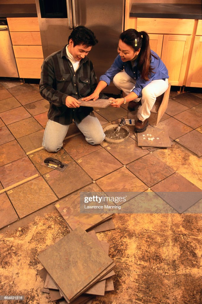 Couple Retiling Their Kitchen Floor Stock Photo   Getty Images