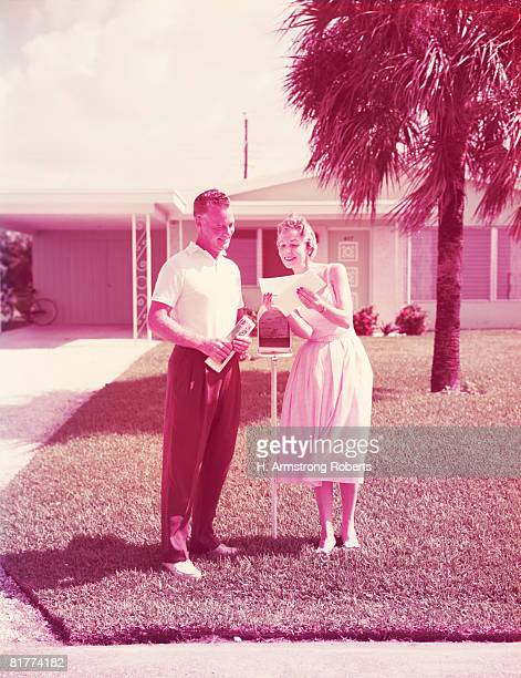 Couple retrieving mail at front yard mailbox. (Photo by H. Armstrong Roberts/Retrofile/Getty Images)