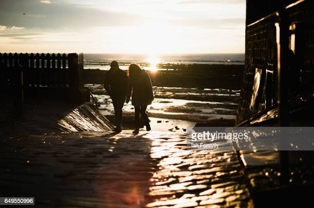A couple return from an early morning walk on the beach as day breaks over Robin Hood's Bay on the North Yorkshire coast on March 8 2017 in Robin...