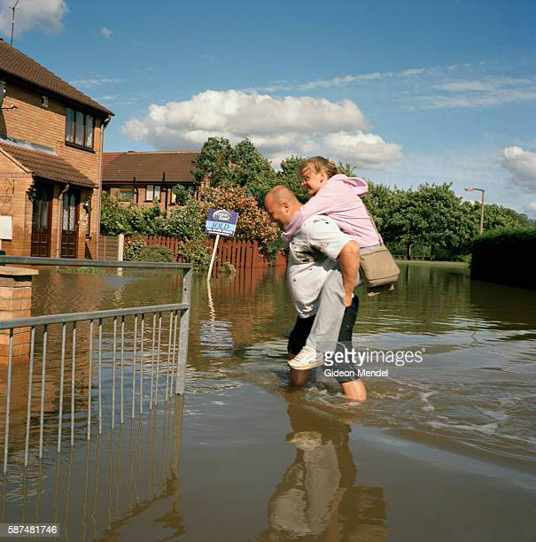 A couple return to their home crossing one of the flooded streets in Catcliffe village This was one of the communities flooded when a freak tropical...