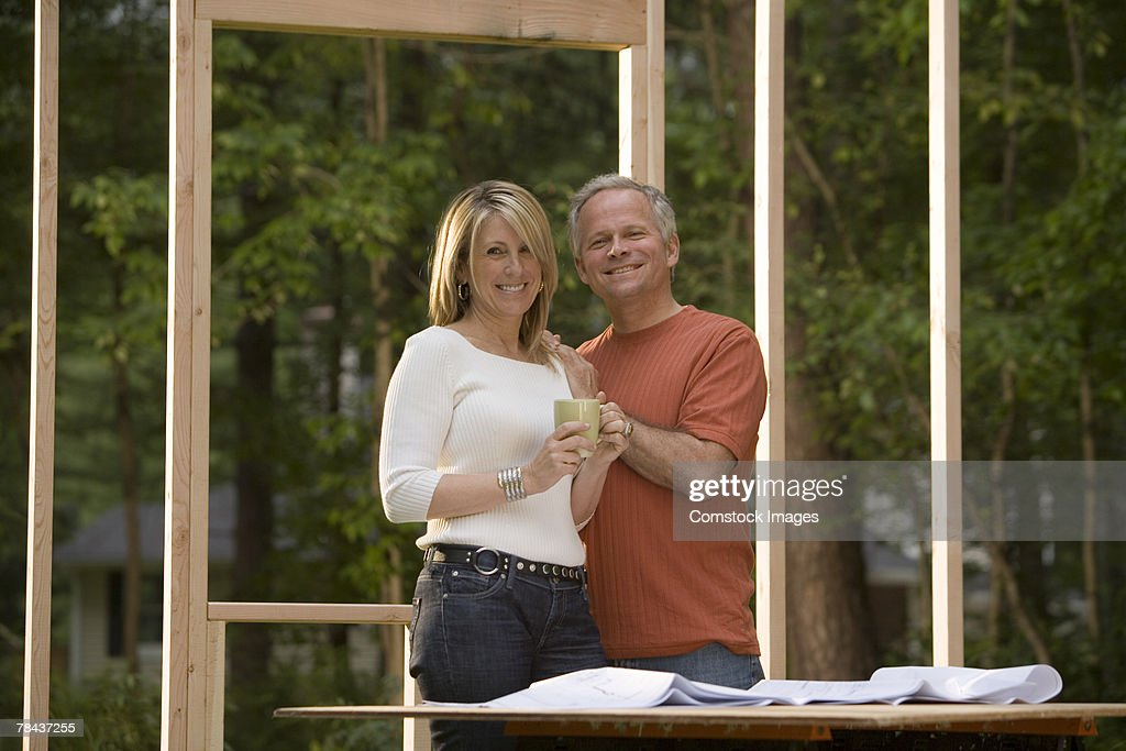 Couple reviewing blueprints at construction site : Stockfoto