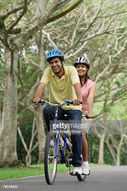 A couple ride a bike together