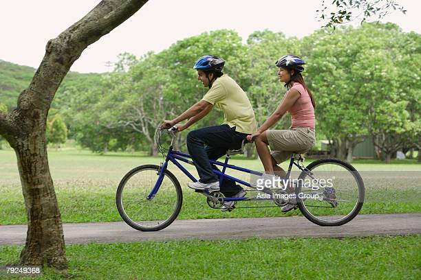 a couple ride a bike together - tandem bicycle stock pictures, royalty-free photos & images