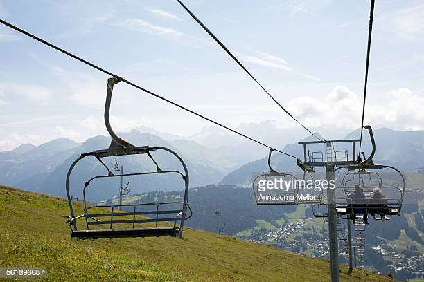 A couple ride a ski lift over the French Alps