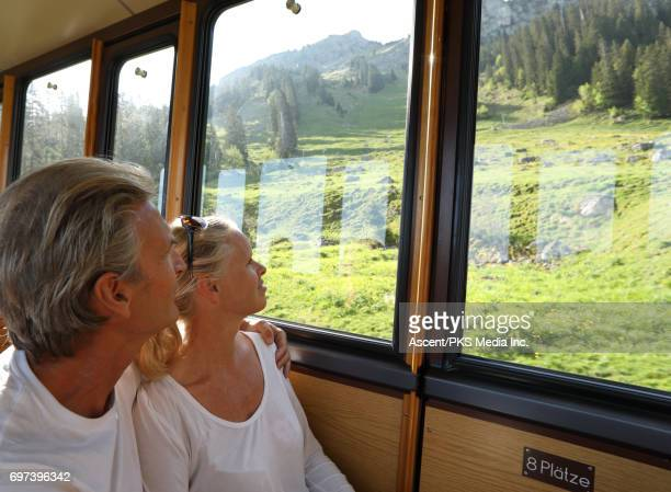Couple ride in old fashioned train above valley, into mountains