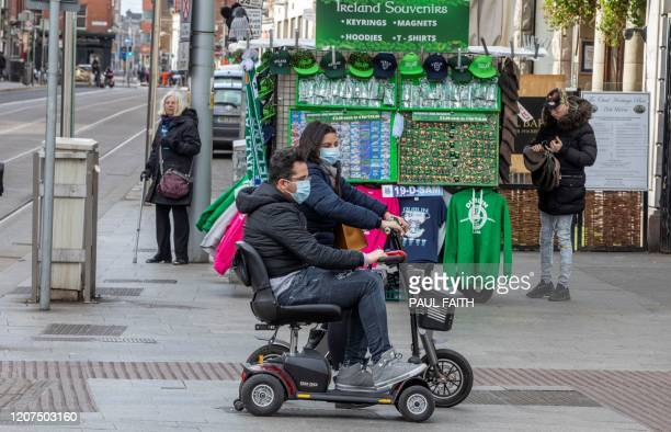 A couple ride in the O'Connell Street area of Dublin on March 17 as St Patrick's Day festivities are cancelled and pubs shut in reaction to the novel...