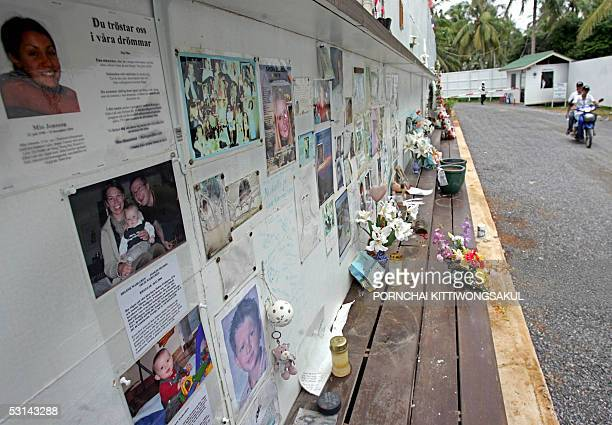 A couple ride past missing persons notice board at the memorial wall near the Maikao mortuary in Phuket southern Thailand 24 June 2005 The December...