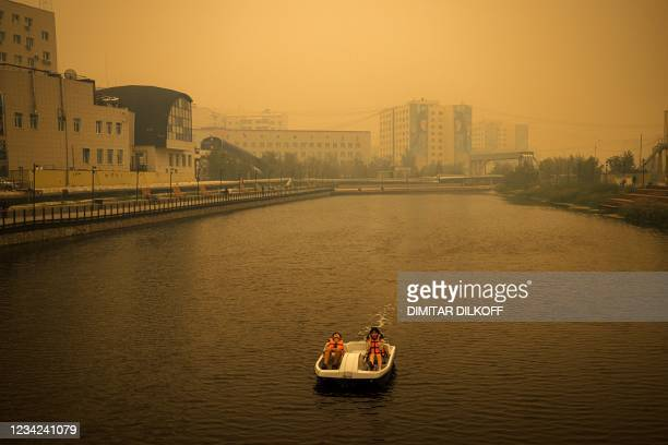 Couple rides a pedal boat as smoke from nearby forest fires hangs over the city of Yakutsk, in the republic of Sakha, Siberia, on July 27, 2021. -...