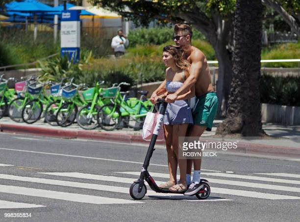 A couple rides a shared electric scooter in Santa Monica California on July 13 2018 Cities across the US are grappling with the growing trend of...