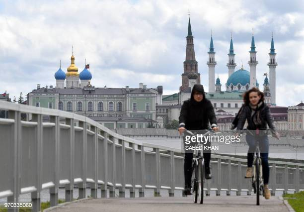A couple rides bikes along a bridge on the Kazanka river with the Kazan Kremlin and the KulSharif mosque seen in the background in Kazan on June 9...