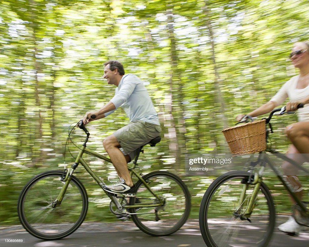 Couple rides bikes on tree lined street : Stock Photo