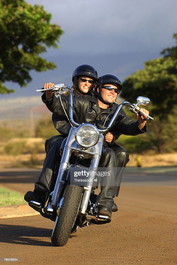 A couple rides their motorcycle on a curvy road toward the viewer. : Stock Photo