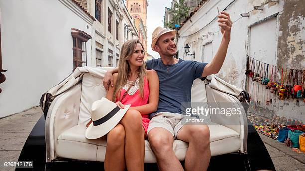 Couple riding a carriage and taking a selfie