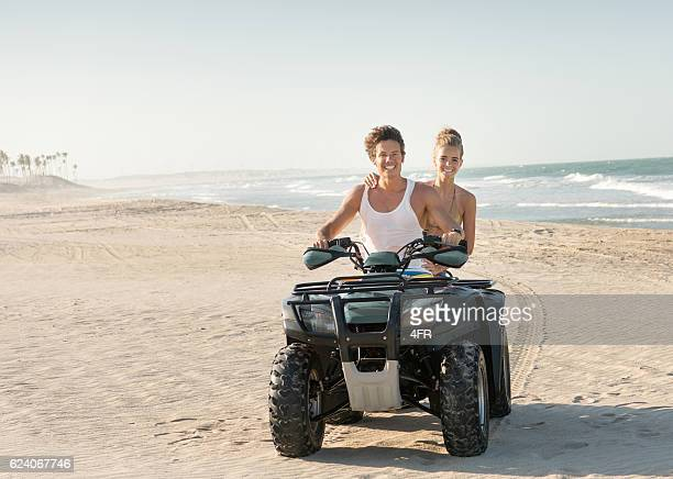 Couple riding a Quad ATV down the Beach