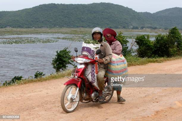 Couple riding a scooter on a country road Cambodia