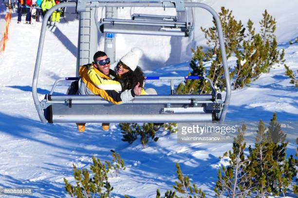 couple riding a ski lift in the mountains - ski lift stock pictures, royalty-free photos & images