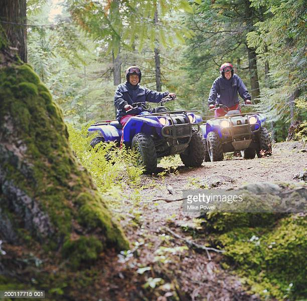 Couple riding ATV's through forest, portrait