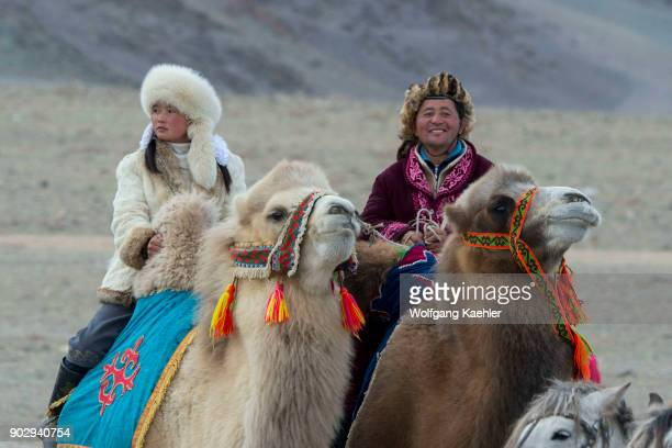 A couple riding Bactrian camels at the Golden Eagle Festival grounds near the city of Ulgii in the BayanUlgii Province in western Mongolia