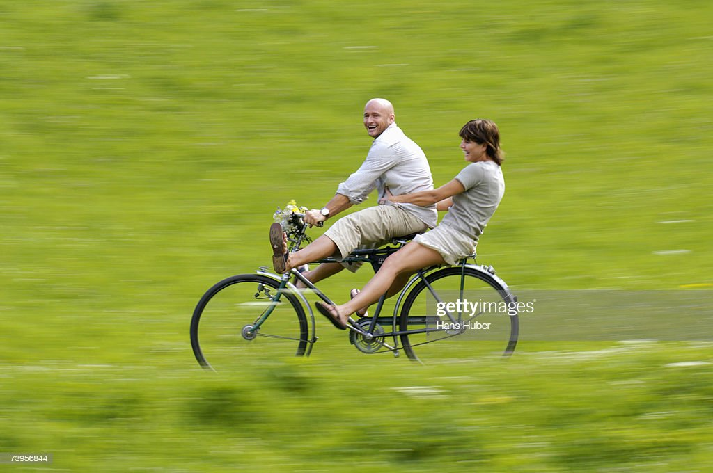 Couple riding bicycle in meadow, side view : Stock-Foto