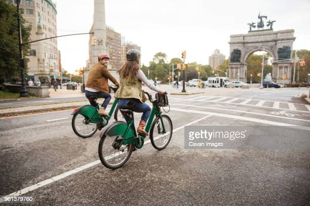 couple riding bicycle on city street - cavan images foto e immagini stock
