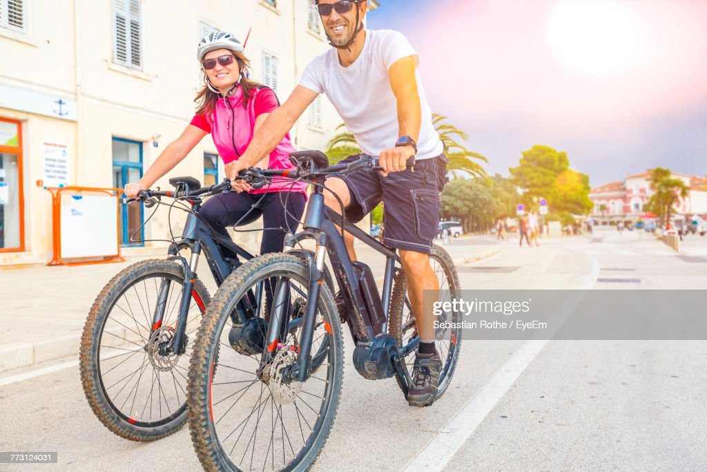 Couple Riding Bicycle On Road Against Sky : Photo