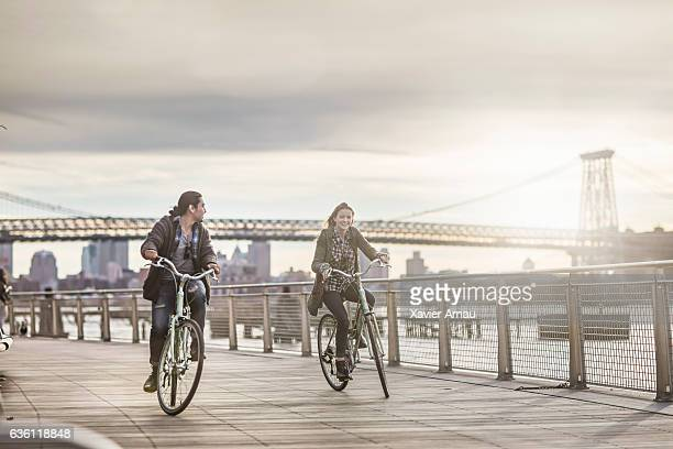 couple riding bicycles against williamsburg bridge - williamsburg new york city stock pictures, royalty-free photos & images