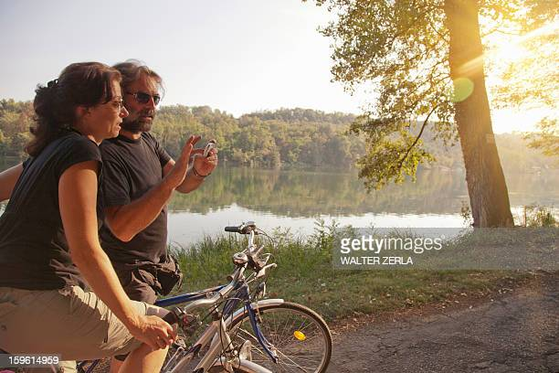 Couple riding bicycles by river bank