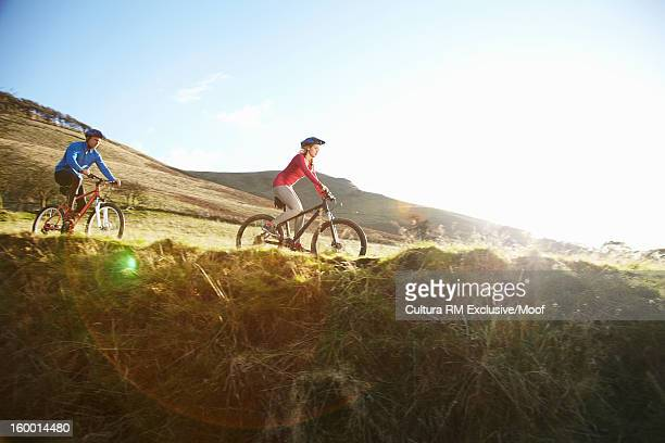 Couple riding bicycles in grassy field