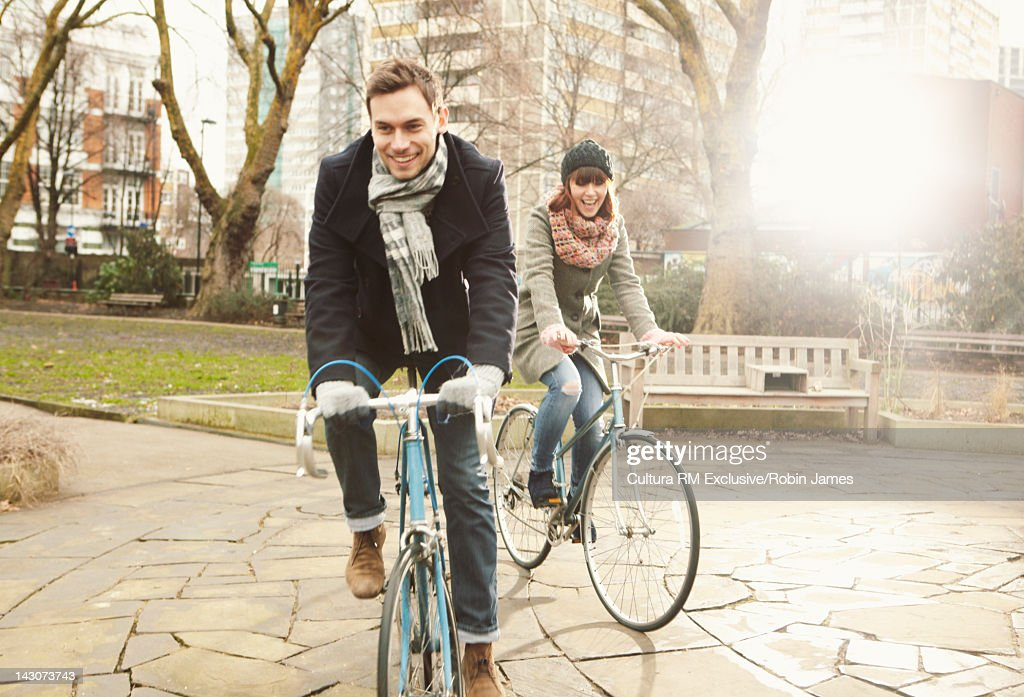 Couple riding bicycles in urban park : ストックフォト