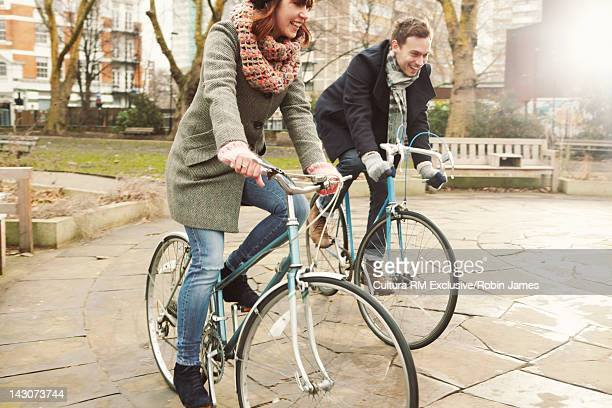 Couple riding bicycles in urban park