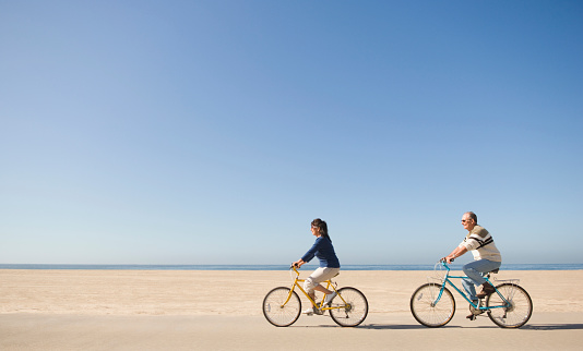 Couple riding bicycles on beach - gettyimageskorea