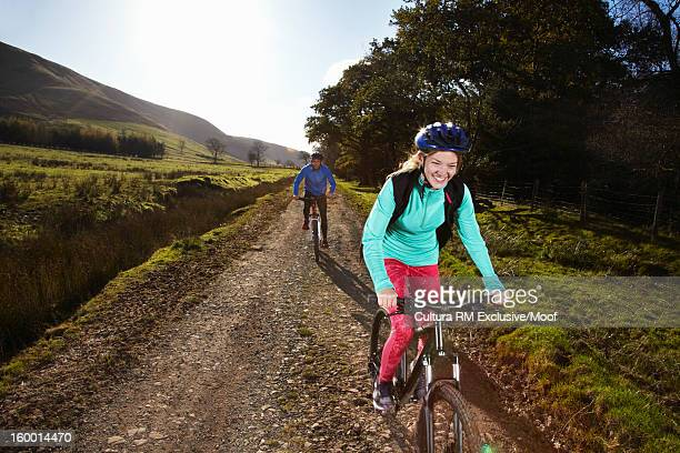 Couple riding bicycles on dirt path