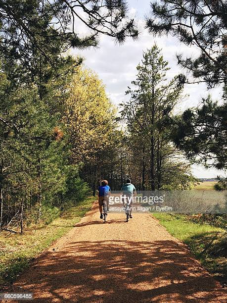 Couple Riding Bicycles On Dirt Road