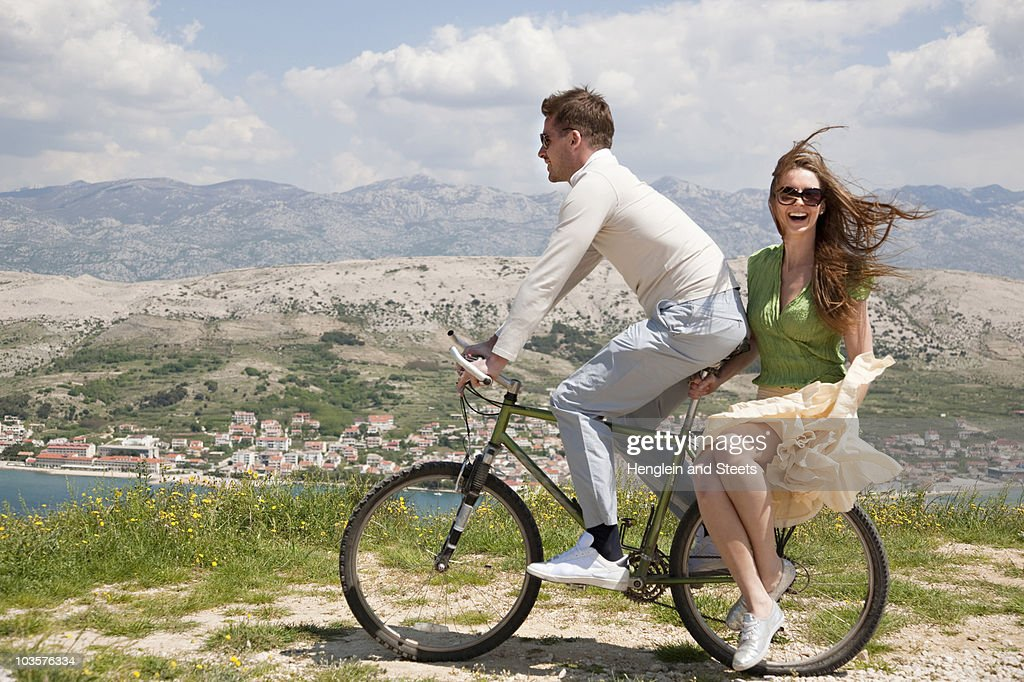 couple riding bike by sea stock photo getty images