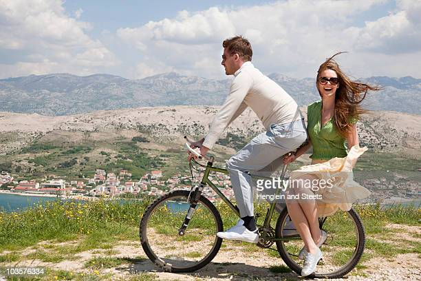 Couple riding bike by sea
